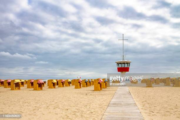 view to beach with hooded beach chairs and attendant's tower, luebeck travemuende, germany - travemünde - fotografias e filmes do acervo