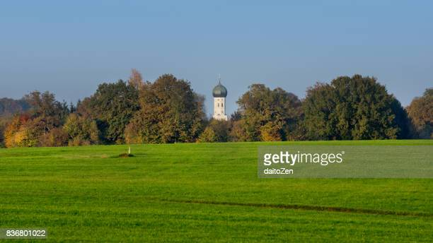 view to münsing church bell tower framed by trees in autumn colors, munsing, upper bavaria, germany - starnberg photos et images de collection