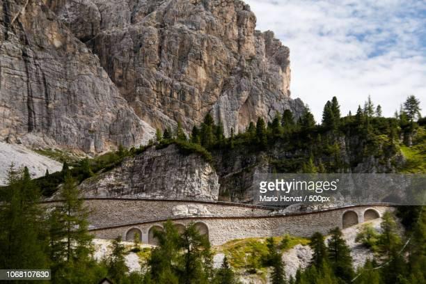 view to mountain road to passo falzarego, dolomites, italy - bergpass stock-fotos und bilder