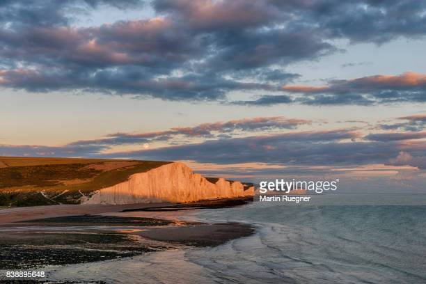view to seven sisters chalk cliffs from cuckmere haven beach, sunset with moon. - seven sisters cliffs stock photos and pictures