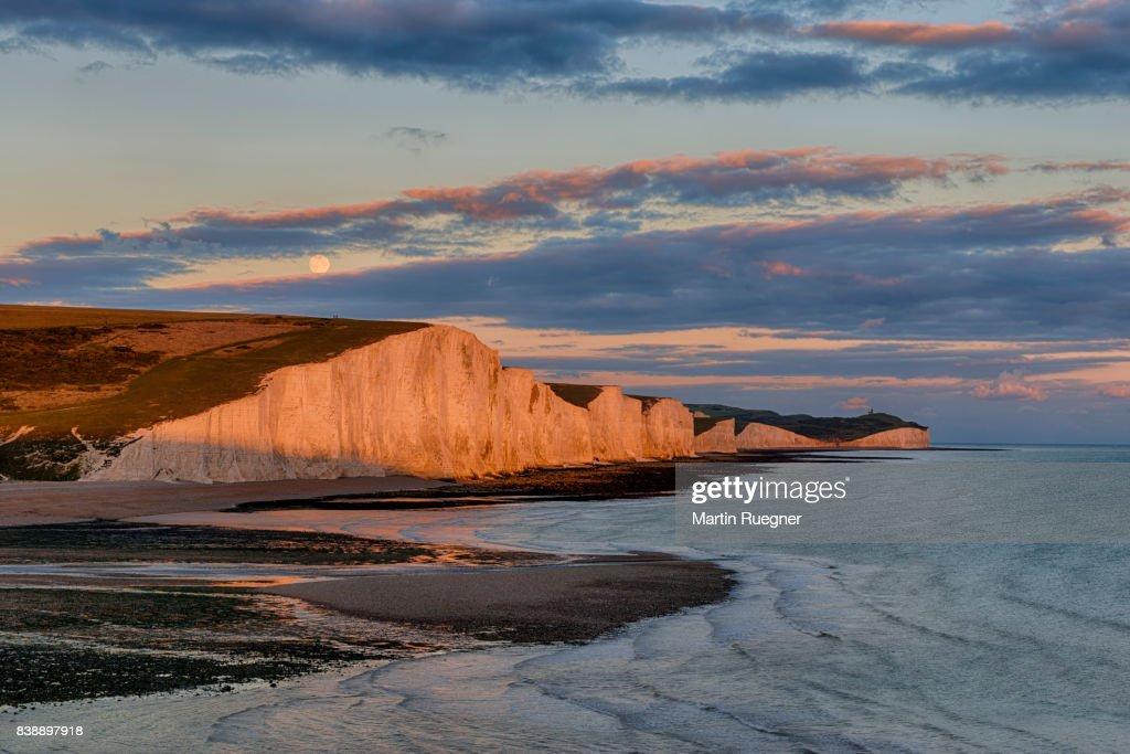 View to Seven Sisters Chalk Cliffs from Cuckmere Haven beach, sunset with moon. : Stock Photo