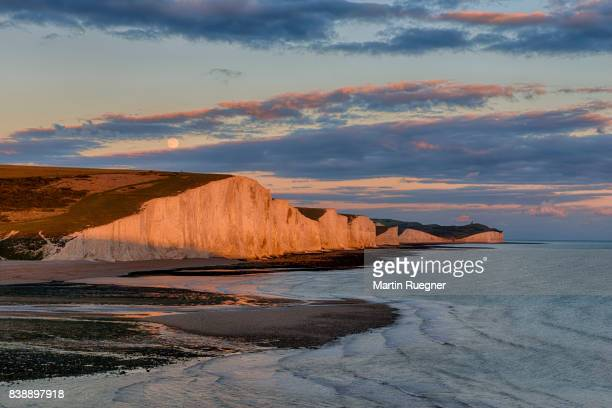 View to Seven Sisters Chalk Cliffs from Cuckmere Haven beach, sunset with moon.