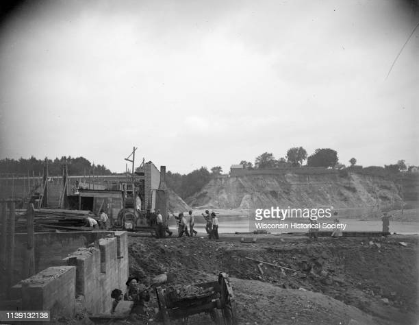 View towards a construction site with people walking on a dirt road and others working at the site Black River Falls Wisconsin 1911 Location...