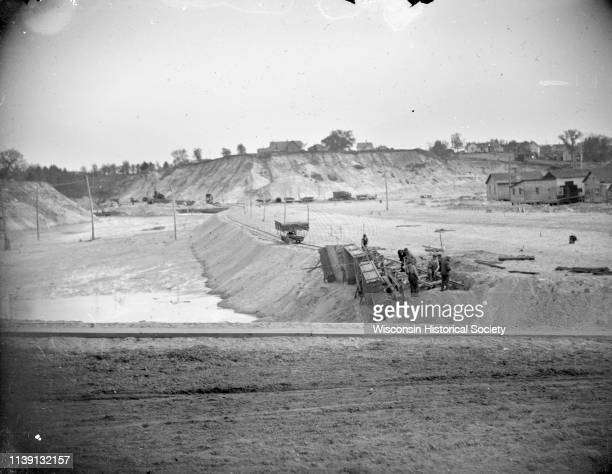 View towards a construction site with wreckage and men working on the wreckage Black River Falls Wisconsin 1911 Location identified as the fill and...