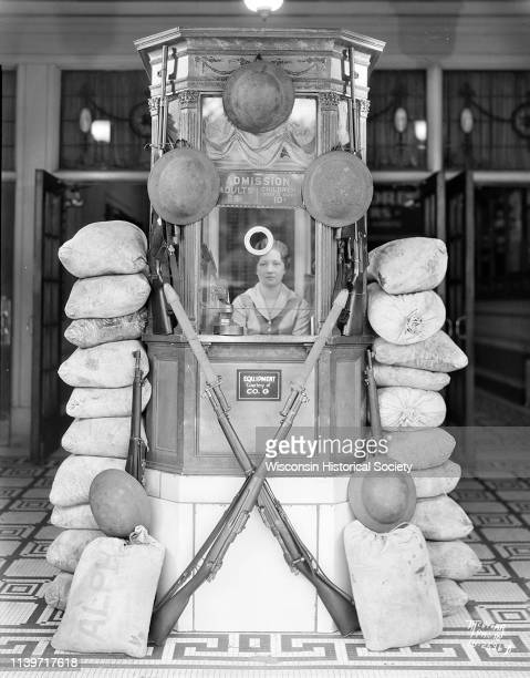 View towards a woman sitting in the Strand Theatre box office surrounded by a display of helmets guns and sand bags for the motion picture 'Women of...