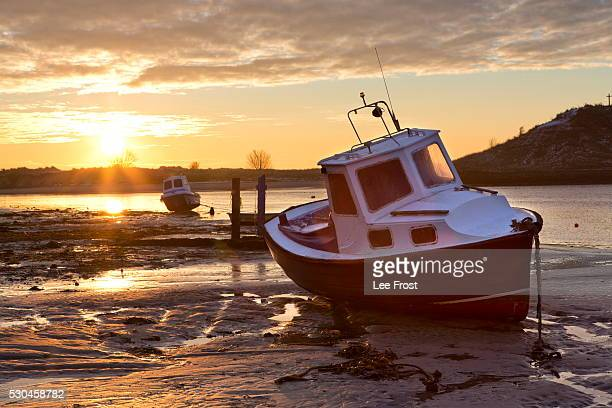 View towards the Aln Estuary during a stunning winter sunrise from the beach at low tide with a fishing boat in the foreground, Alnmouth, near Alnwick, Northumberland, England, United Kingdom, Europe