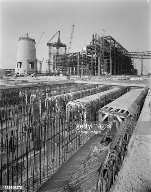 View towards the power house and main chimney during the construction of the Isle of Grain Power Station, showing the five flumes for the cooling...