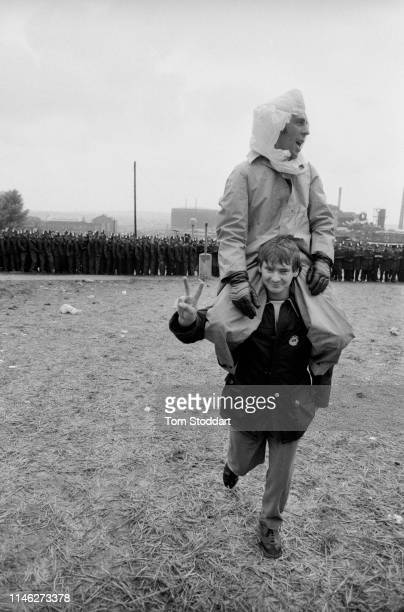 View Two striking miners on atop the shoulders of the other as they walk across a field from a line of police officers near the Orgreave coking plant...