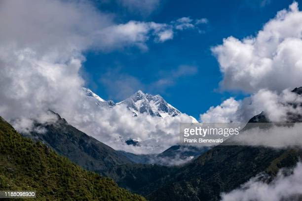 View up the Dudh Koshi valley with a snow-covered peak and mountainous landscape covered in monsoon clouds in the distance.