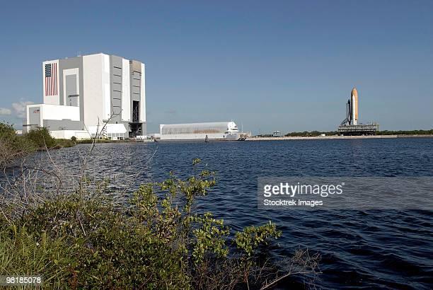 Viewed across the basin, Space Shuttle Atlantis crawls toward the launch pad.