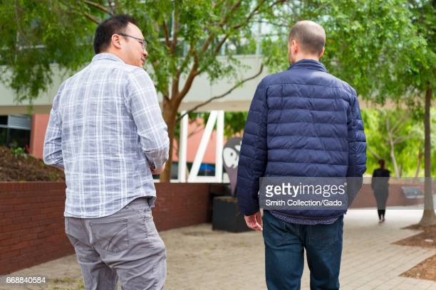 Viewed from behind two middle aged Google Inc employees walk and converse at the Googleplex headquarters of Google Inc in the Silicon Valley town of...