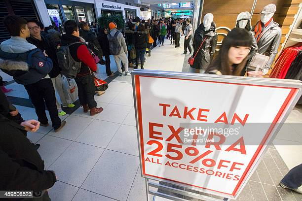 TORONTO ON DECEMBER 26 Viewed from neighbouring store shoppers stand in line specifically to get a pair of 'Jordan 12' running shoes for $200 per...