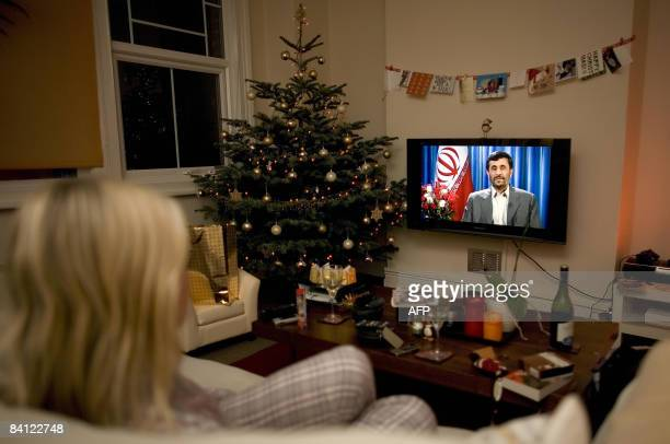 A viewer watches a transmission of Iranian President Mahmoud Ahmadinejad delivering on Britain's Channel 4 an alternative Christmas message to...