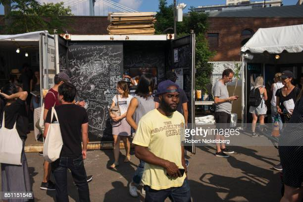 Viewers move through photography exhibits at the sixth annual Photoville event September 17 2017 below the Brooklyn Bridge in Brooklyn New York...