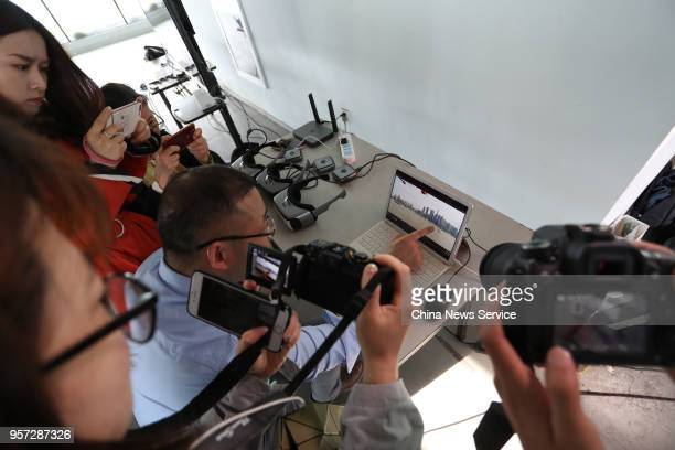 Viewers takes photo during an unmanned aerial vehicle carrying a 5G communication technology module fly along the Huangpu River on May 10 2018 in...