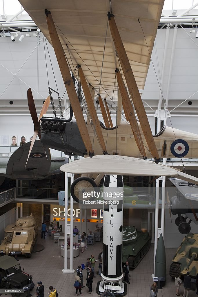 Viewers walk through the first floor displays of World War l and ll military equipment July 3, 2012 on exhibit with a British WW l observation bi-plane hanging at the Imperial War Museum in London, England. Founded in 1917, the museum houses armored vehicles, rockets, planes, weapons, vessels and exhibits from both world wars and recent conflicts.