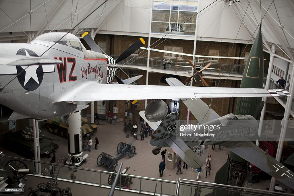 Viewers walk through the first floor of World War 1 and ll displays on exhibit with a WW ll US-made P-51D Mustang hanging at the Imperial War Museum July 3, 2012 in London, England. Founded in 1917, the museum houses armored vehicles, rockets, planes, weapons and exhibits from both world wars and recent conflicts.