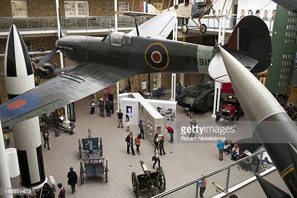 Viewers walk through the first floor of World War 1 and ll displays on exhibit with a British Spitfire Ia hanging at the Imperial War Museum in...