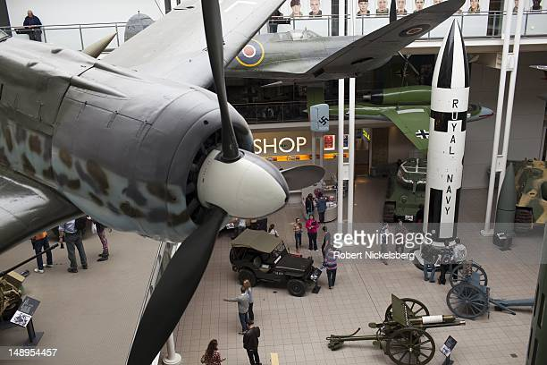 Viewers walk through the first floor of World War 1 and ll exhibit with a German WW ll Messerschmidt fighter plane hanging at the Imperial War Museum...