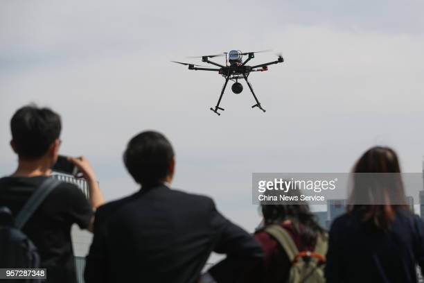 Viewers watch an unmanned aerial vehicle carrying a 5G communication technology module take off along the Huangpu River on May 10 2018 in Shanghai...