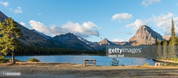 viewing bench at the mountain lake, two medicine lake, mountain landscape, sinopah mountain, glacier national park, montana, usa - two medicine lake montana stock photos and pictures