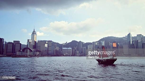 Viewing from Tsim Sha Tsui Promenade, a junk boat crosses to Hong Kong Island.