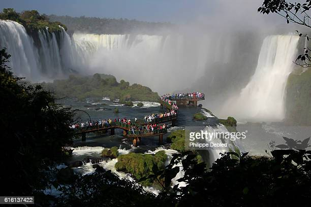 Viewing platform with tourists over the Iguazu River and Panorama of the Iguazu Falls with, from the left to the right, Floriano Falls, Devil's Throat and Belgrano Falls. Foz do Iguaçu, Paraná State, Brazil