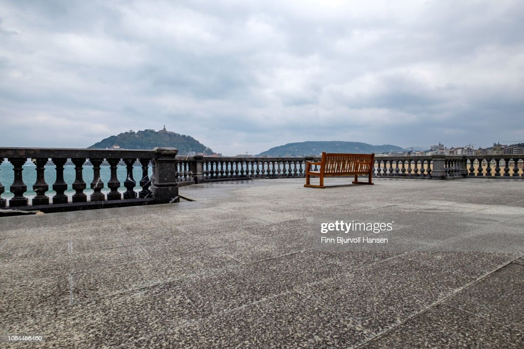 Viewpoint at the beach of San Sebastian Spain. Concrete fence and a red bench. City in the background : Stock Photo