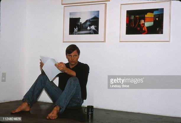 Viggo Mortensen sits on floor reviewing list of artworks at his exhibition Recent Forgeries at Track 16 Gallery at Bergamot Station on November 23...