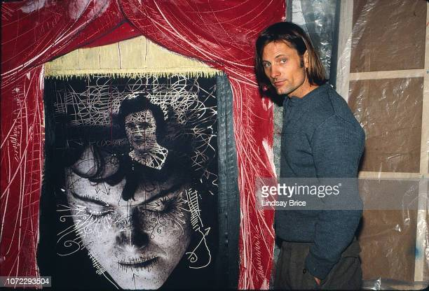 Viggo Mortensen stands beside a painting featuring an image of Exene Cervenka inside the warehouse loft in which he lived and painted for the film A...