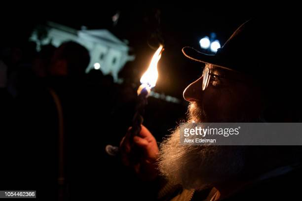 A vigil participant holds a Havdalah candle during a Havdalah vigil for the victims of the Tree of Life Congregation shooting in front of the White...