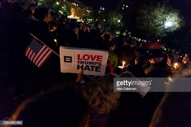 A vigil participant holds a 'Love Trumps Hate' sign during a Havdalah vigil for the victims of the Tree of Life Congregation shooting in front of the...