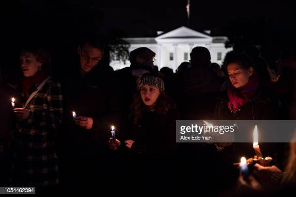 Vigil participants hold candles and sing a Jewish prayer during a Havdalah vigil for the victims of the Tree of Life Congregation shooting in front...