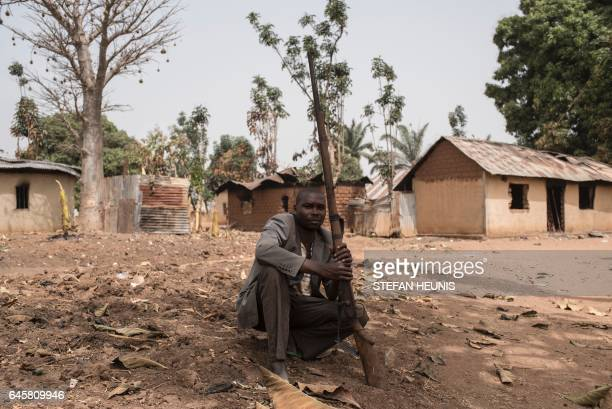 TOPSHOT A vigilante sits on the ground with his gun in the village of Bakin Kogi in Kaduna state northwest Nigeria that was recently attacked by...