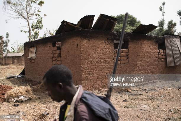 A vigilante walks through the village of Bakin Kogi in Kaduna state northwest Nigeria that was recently attacked by suspected Fulani herdsmen on...