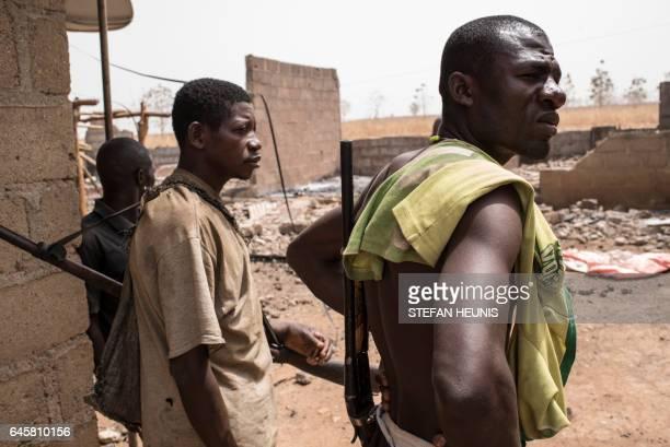 Vigilantes survey the damage in the village of Bakin Kogi in Kaduna state northwest Nigeria that was recently attacked by suspected Fulani herdsmen...