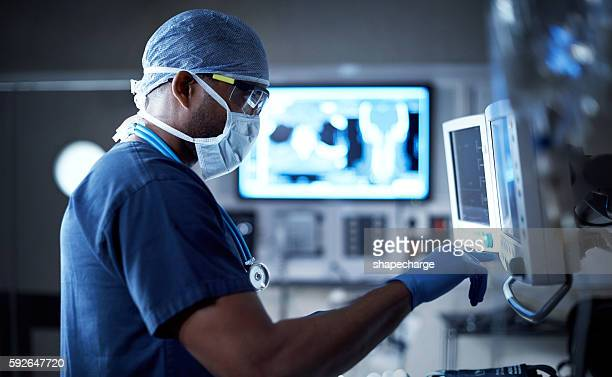 vigilantly monitoring his patient's vitals - medical procedure stock pictures, royalty-free photos & images