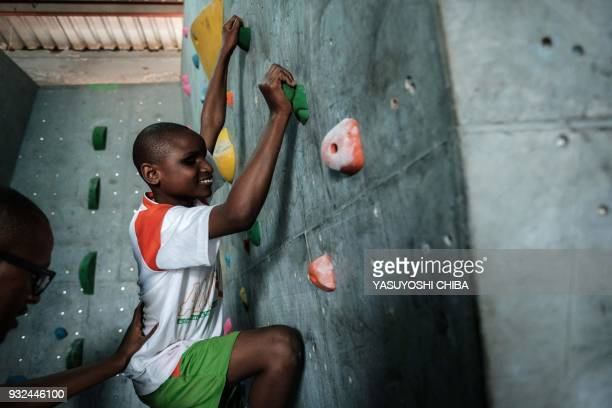 Viginiah Wanjiru of Thika school for the Blind challenges bouldering on the artificial climbing wall during a weeklong free climbing training by the...