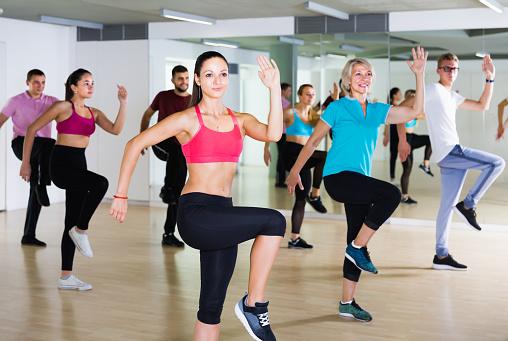 vigorous men and ladies dancing aerobics at lesson 932334312