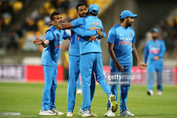 Vijay Shankar of India celebrates with Dinesh Karthik after taking the wicket of Colin Munro of New Zealand during game one of the International T20...
