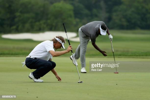 Vijay Singh and Bernhard Langer line up putts on the 16th green during the final round of the Senior PGA Championship at Trump National Golf Club on...