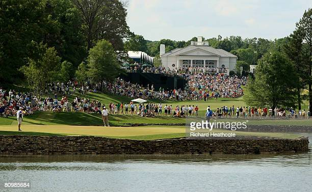 Vijay Singh and Freddie Couples on the 17th green as crowds gather around the 18th green and clubhouse in the distance during the final round of the...