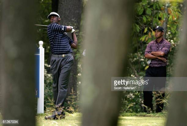 Vijay Singh of Fiji hits his tee shot on the 5th hole as Tiger Woods watches during the Deutsche Bank Championship on September 6, 2004 at the TPC of...