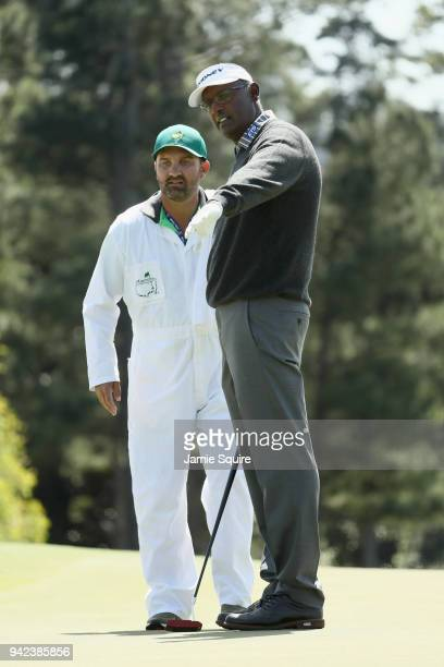 Vijay Singh of Fiji lines up a putt with caddie Danny Sahl on the 18th green during the first round of the 2018 Masters Tournament at Augusta...