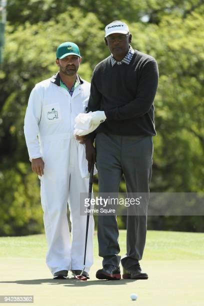 Vijay Singh of Fiji lines up a putt with his caddie Danny Sahl during the first round of the 2018 Masters Tournament at Augusta National Golf Club on...