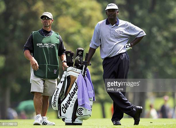 Vijay Singh of Fiji waits in the fairway to hit his second shot on the par 4 18th hole close to the hole during the first round of the Buick Open on...