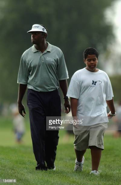 Vijay Singh of Fiji walks back to the clubhouse with his son Qass as rainh suspends play during the first round on August 15, 2002 for the PGA...