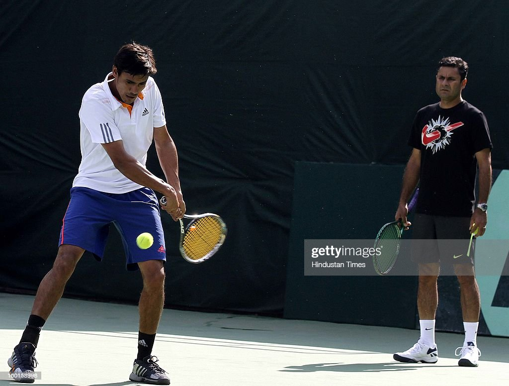 Vijayant Malik member of India Davis cup team plays a shot as coach Zeeshan Ali looks on during practice session at Delhi Lawn Tennis Association on January 27, 2013 in New Delhi, India.