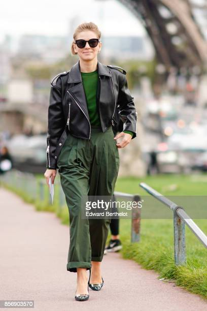 Vika Gazinskaya wears a black leather perfecto jacket a green top green pants outside Hermes during Paris Fashion Week Womenswear Spring/Summer 2018...