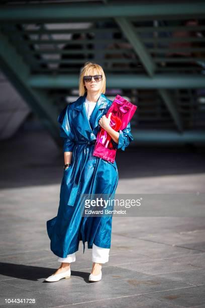 Vika Gazinskaya wears a blue leather trench coat a pink bag outside Giambattista Valli during Paris Fashion Week Womenswear Spring/Summer 2019 on...